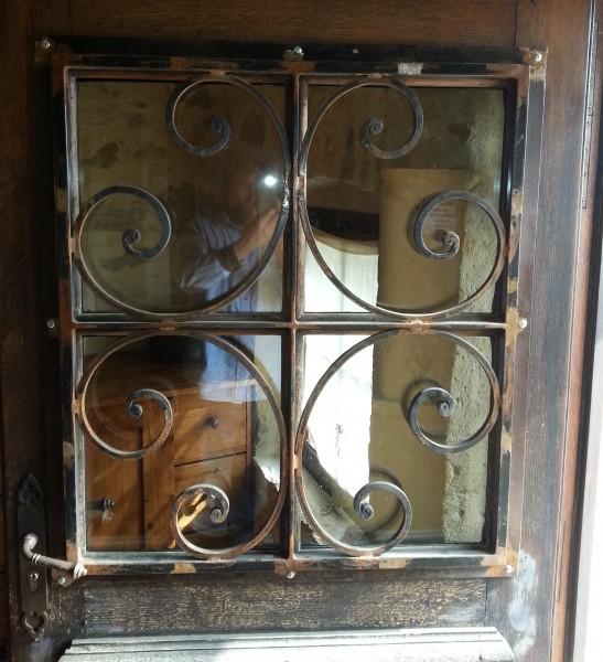 Grille de défense en fer forgé installé sur une porte en Bois à Uzés